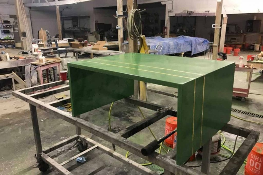 green concrete coffee table with embedded brass strips in shop