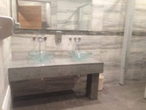thick concrete vanity with glass vessel sinks