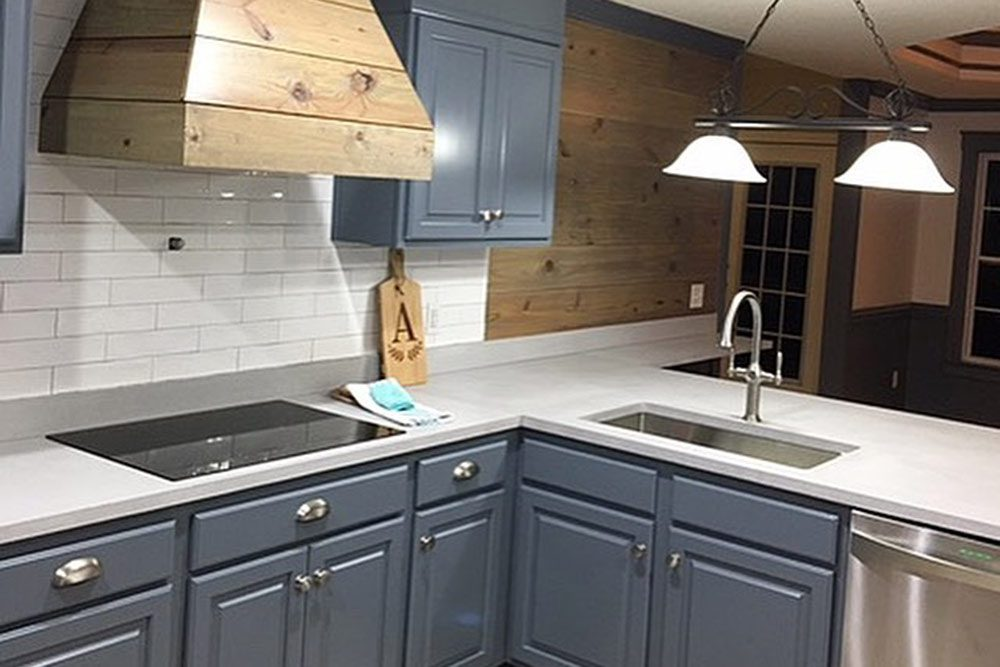 pale gray concrete countertop on blue cabinets in kitchen