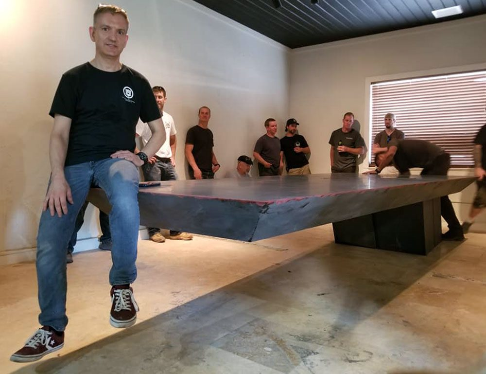 Jeff Girard sitting on cantilevered concrete table