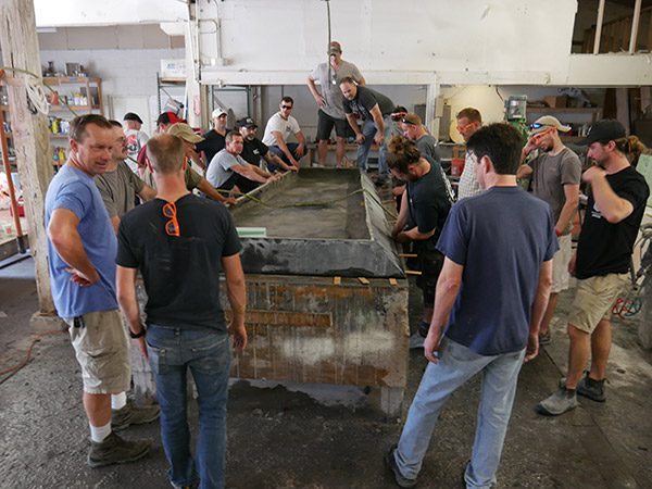 getting ready to lift large concrete table top off casting table