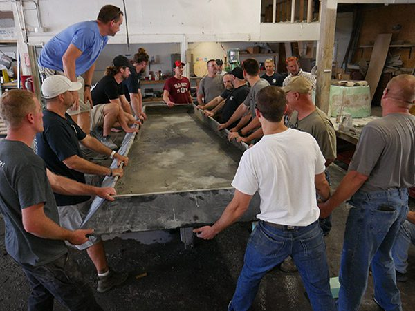 lots of men gathered around large concrete table top on casting table