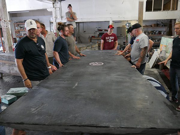 inspecting large concrete table top on casting table