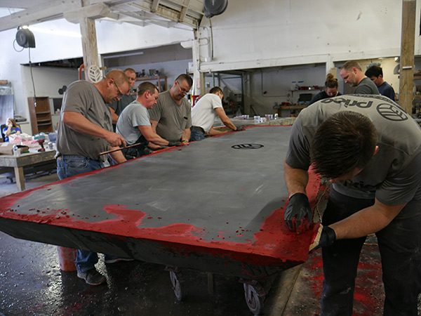 grouting edges of large concrete table top with red concrete