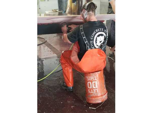 sitting on bucket to wet grind edges of large concrete table top