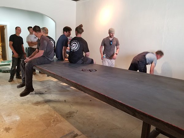 4 people sitting on edge of 11 foot cantilevered concrete table