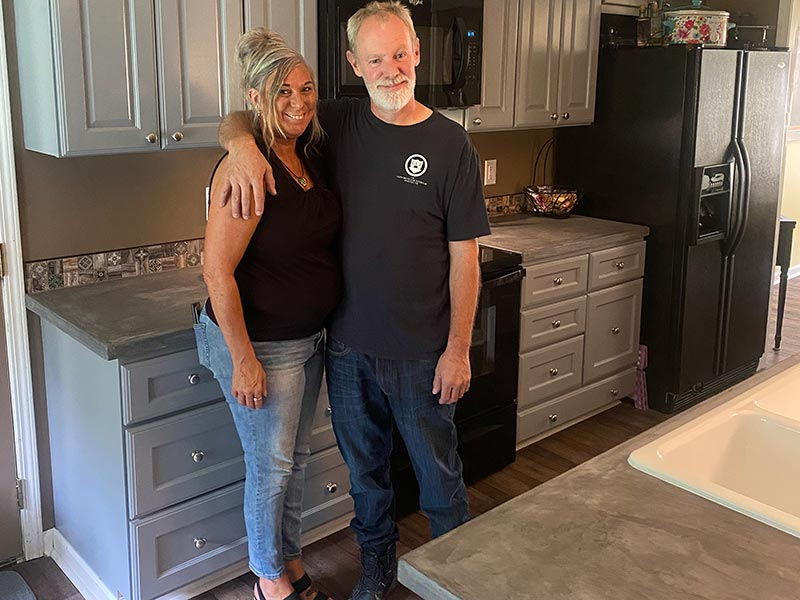 DIY concrete countertops husband and wife smiling in kitchen