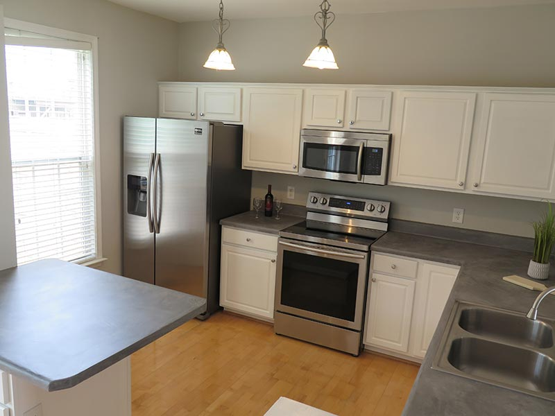 after kitchen with gray concrete countertops and white painted cabinets Yvette
